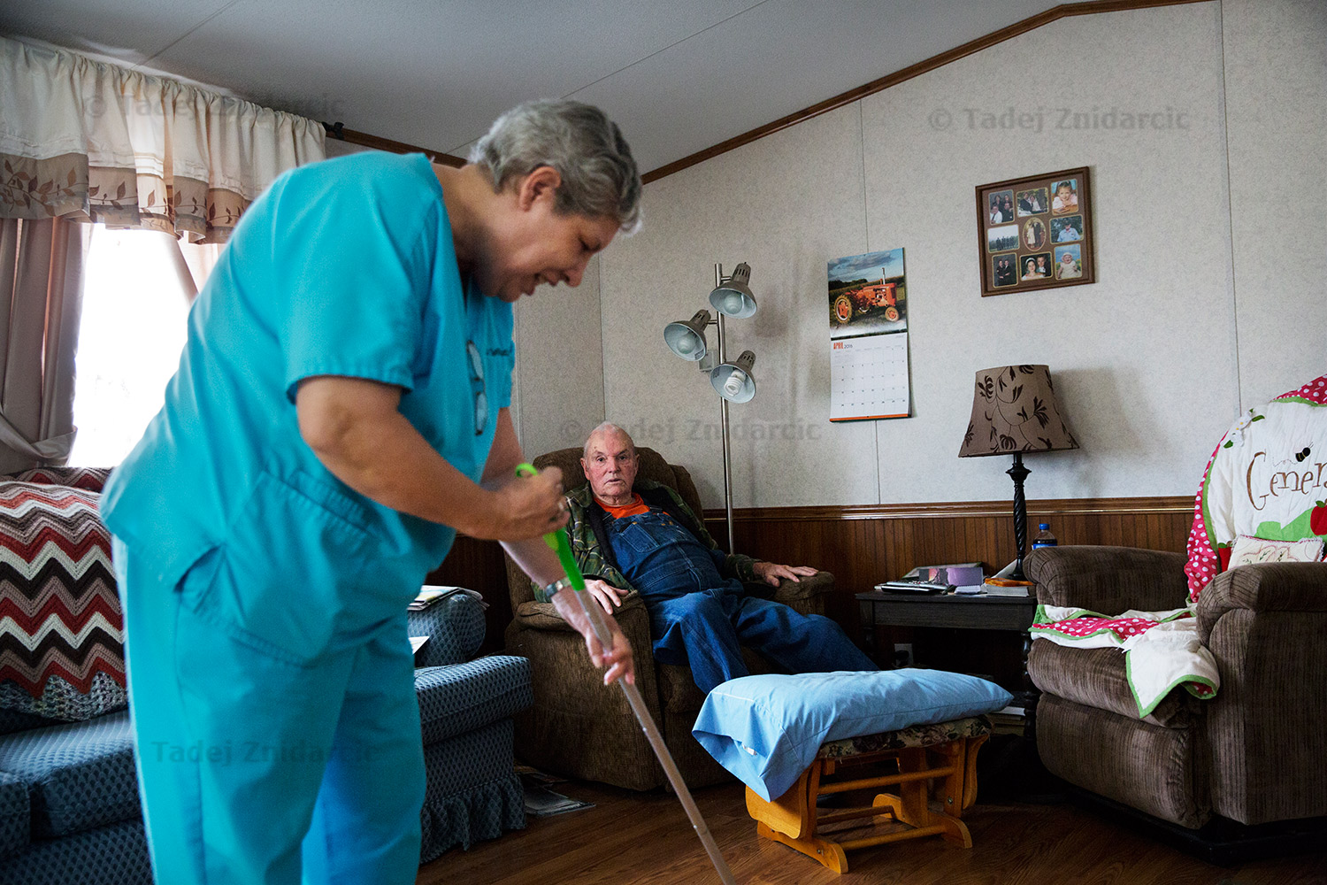 Home care aide Diana chats with Walter while cleaning the floor of his home.
