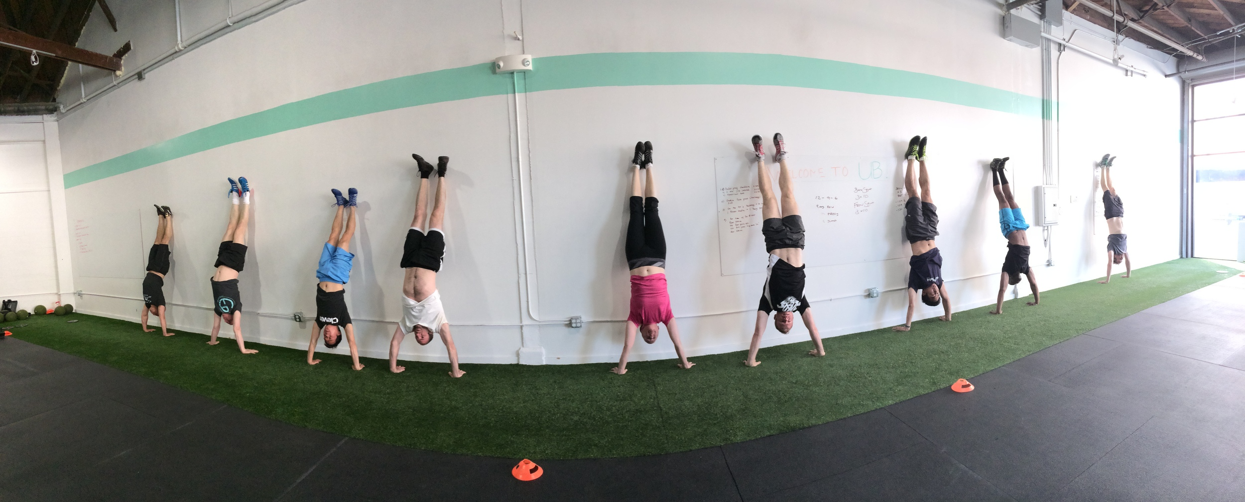 The 8am class works their shoulder stability with handstand holds