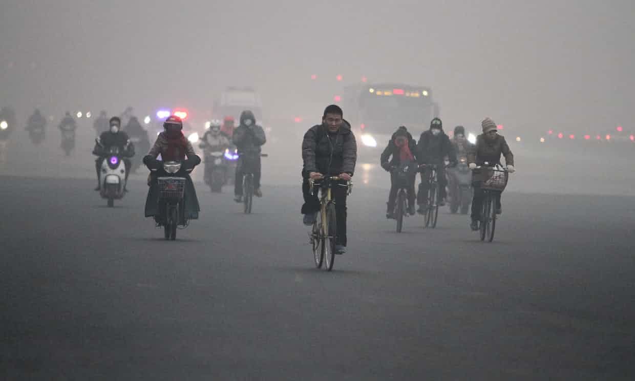 People cycle in heavy smog in Beijing. Photograph: Imaginechina/Rex/Shutterstock
