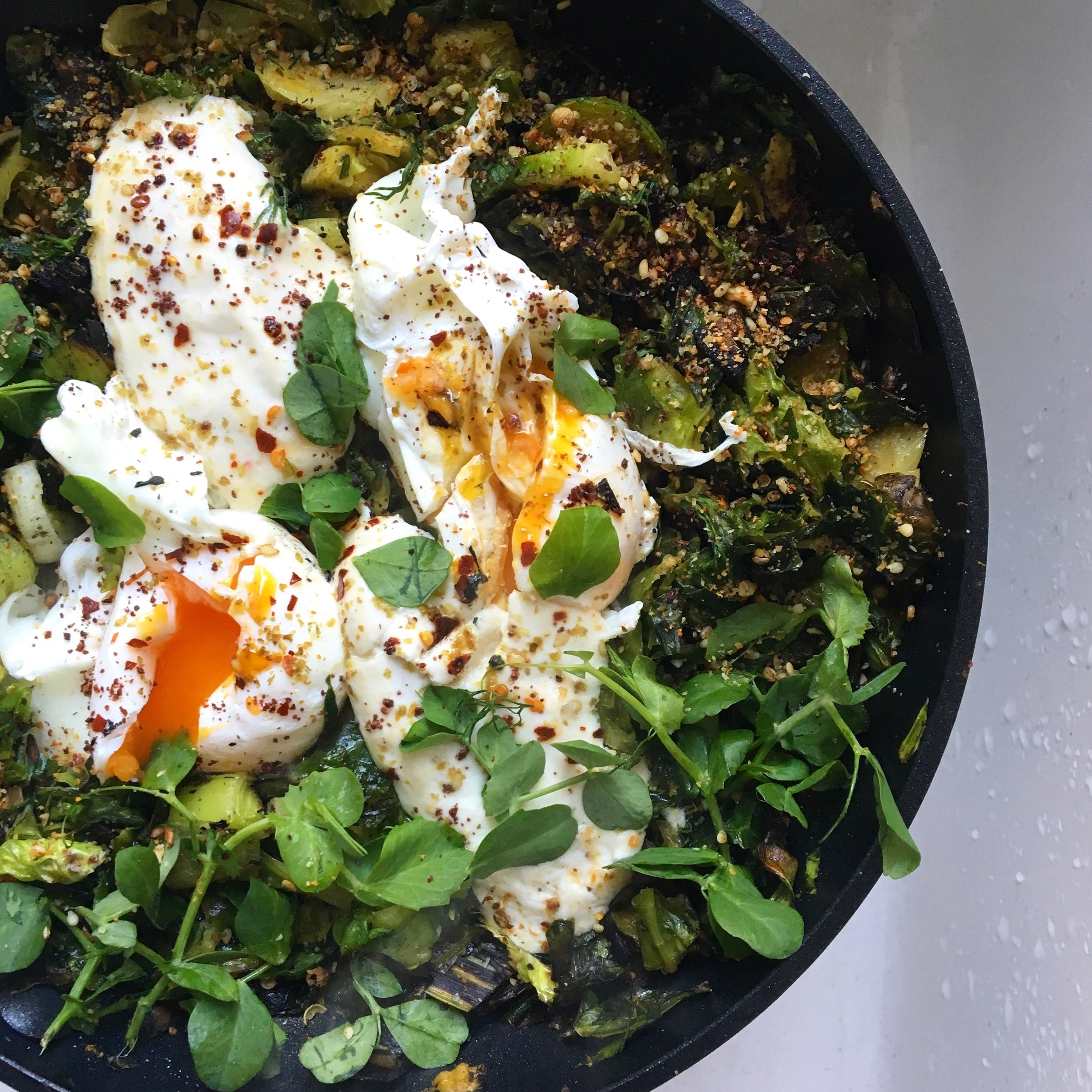 Green shakshuka topped with tahini yoghurt, preserved lemon, chilli flakes and dukkah.