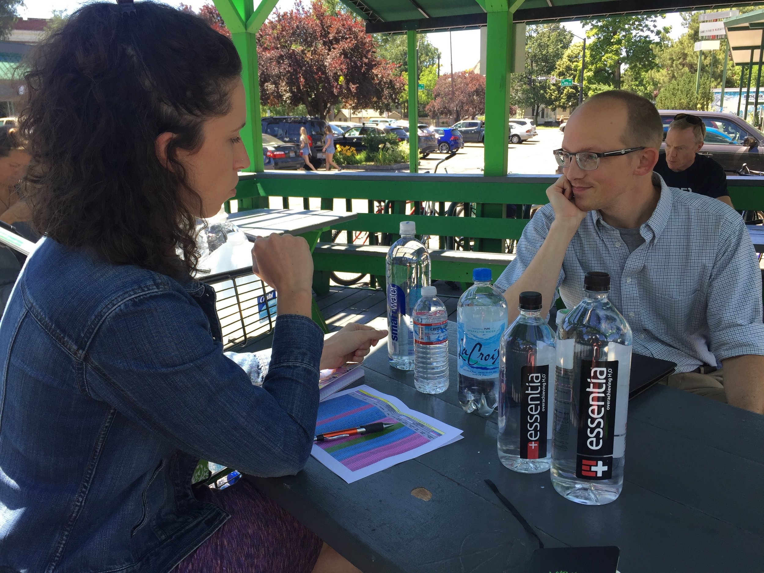 "Above and below: Our Purchasing Coordinator Eileen meets with Evan, an Environmental Analyst from the City of Boise to review our water bottle selection. Evan gives each bottle the ""crinkle test"" to help determine whether or not it is recyclable under the new guidelines."