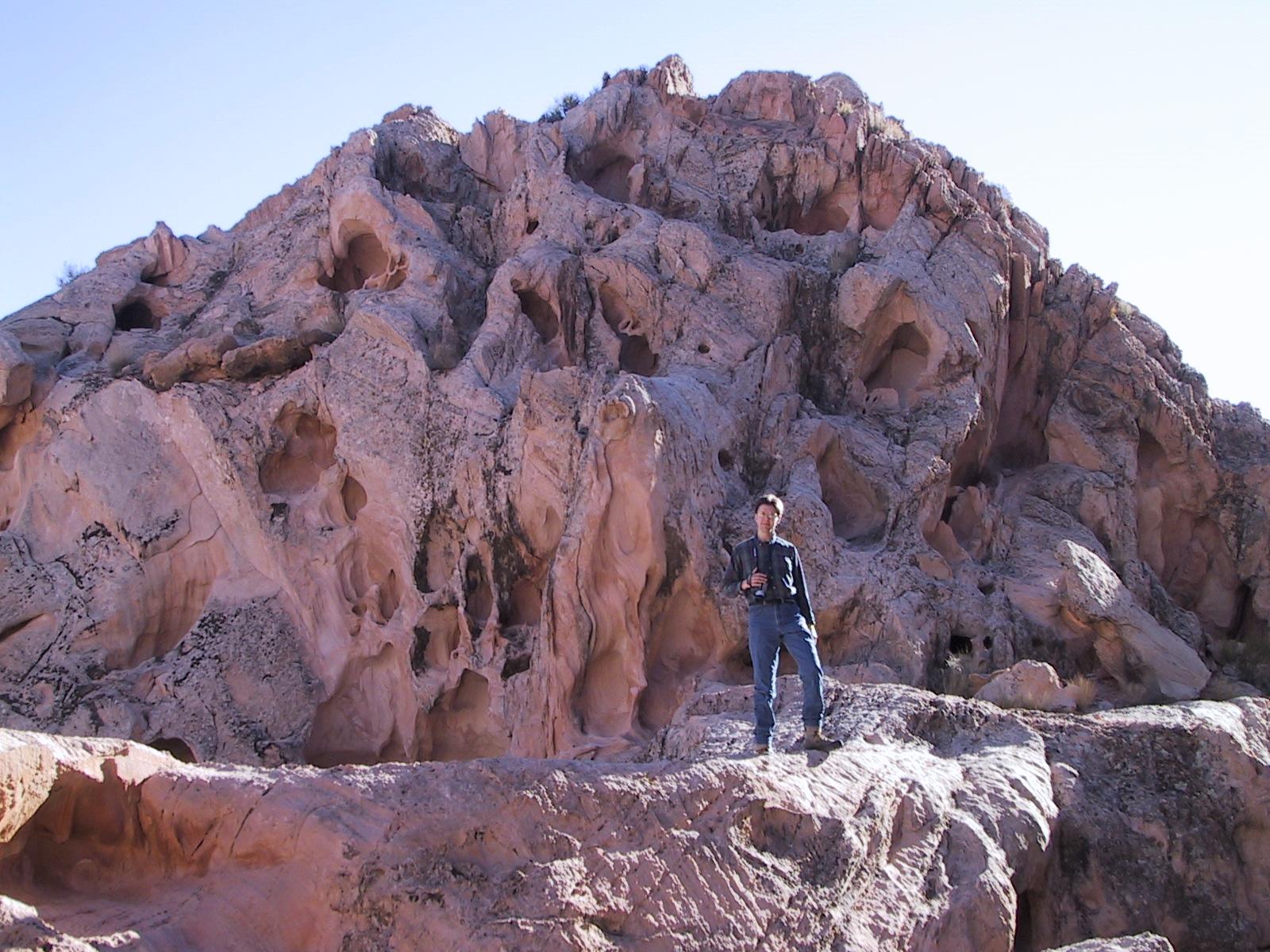 Joe posing in front of an eroded rock hill