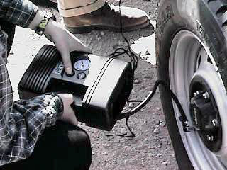 Anne is filling the tire up to regulation air pressure.