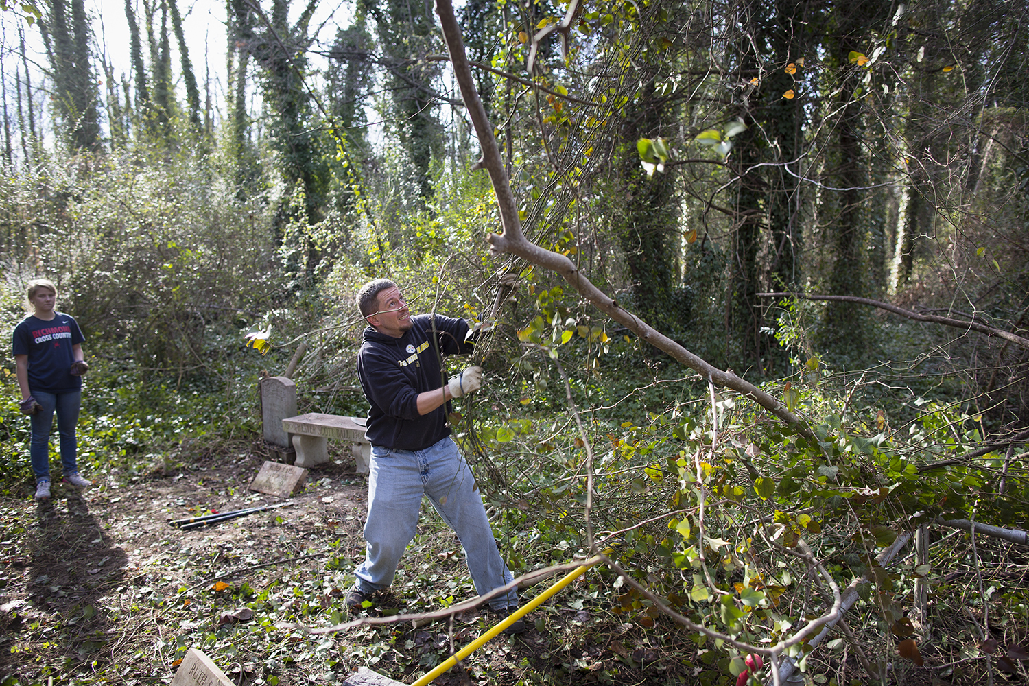 Volunteer Justin tugs at vines ensnaring tree branches during East End Cemetery work day, January 2015.©brianpalmer.photos 2015