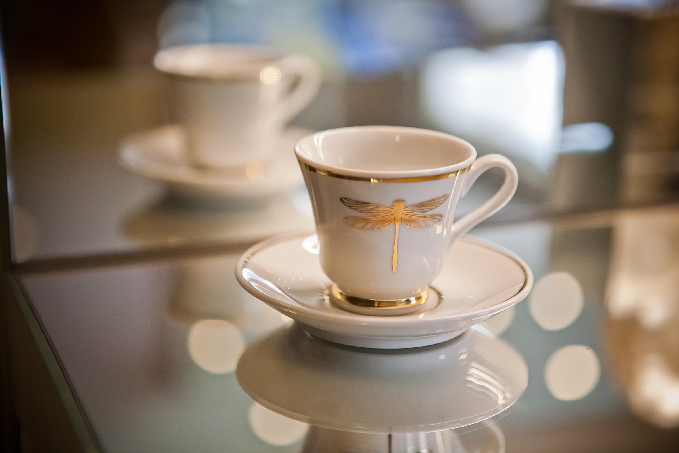 Detalhe xícara de libélula pintada à mão com tinta a base de ouro.