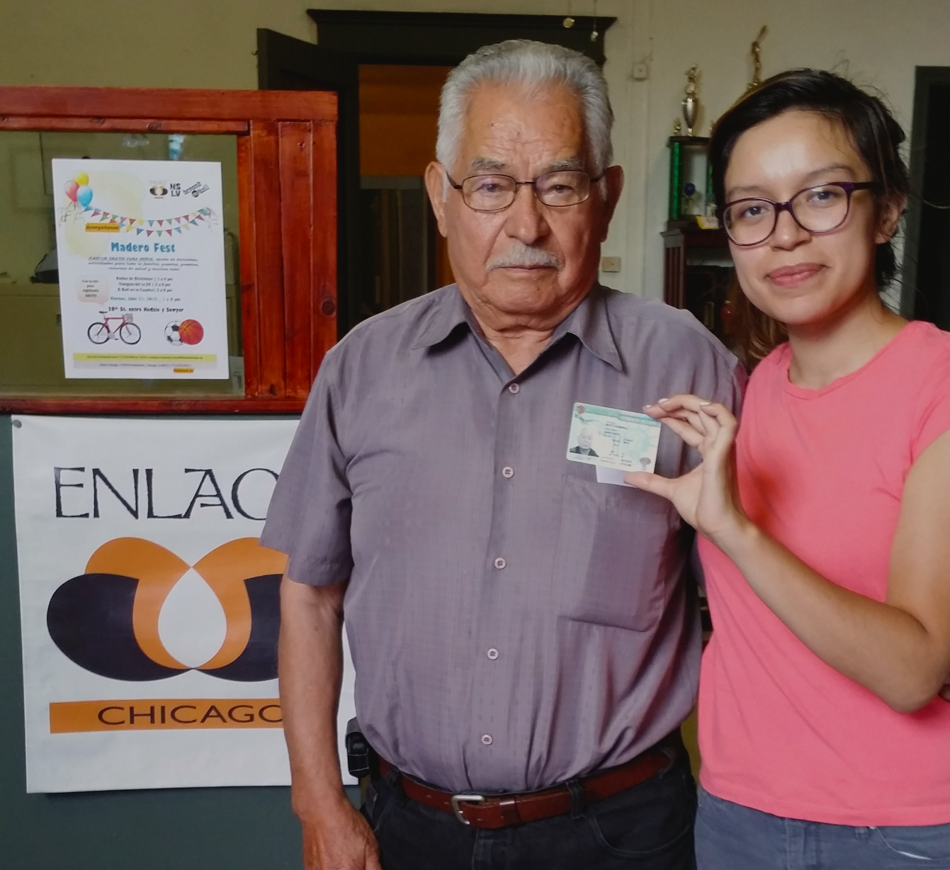 Enlace Immigration & Legal Services Coordinator Lulu Martinez and one of our clients celebrate his new green card.