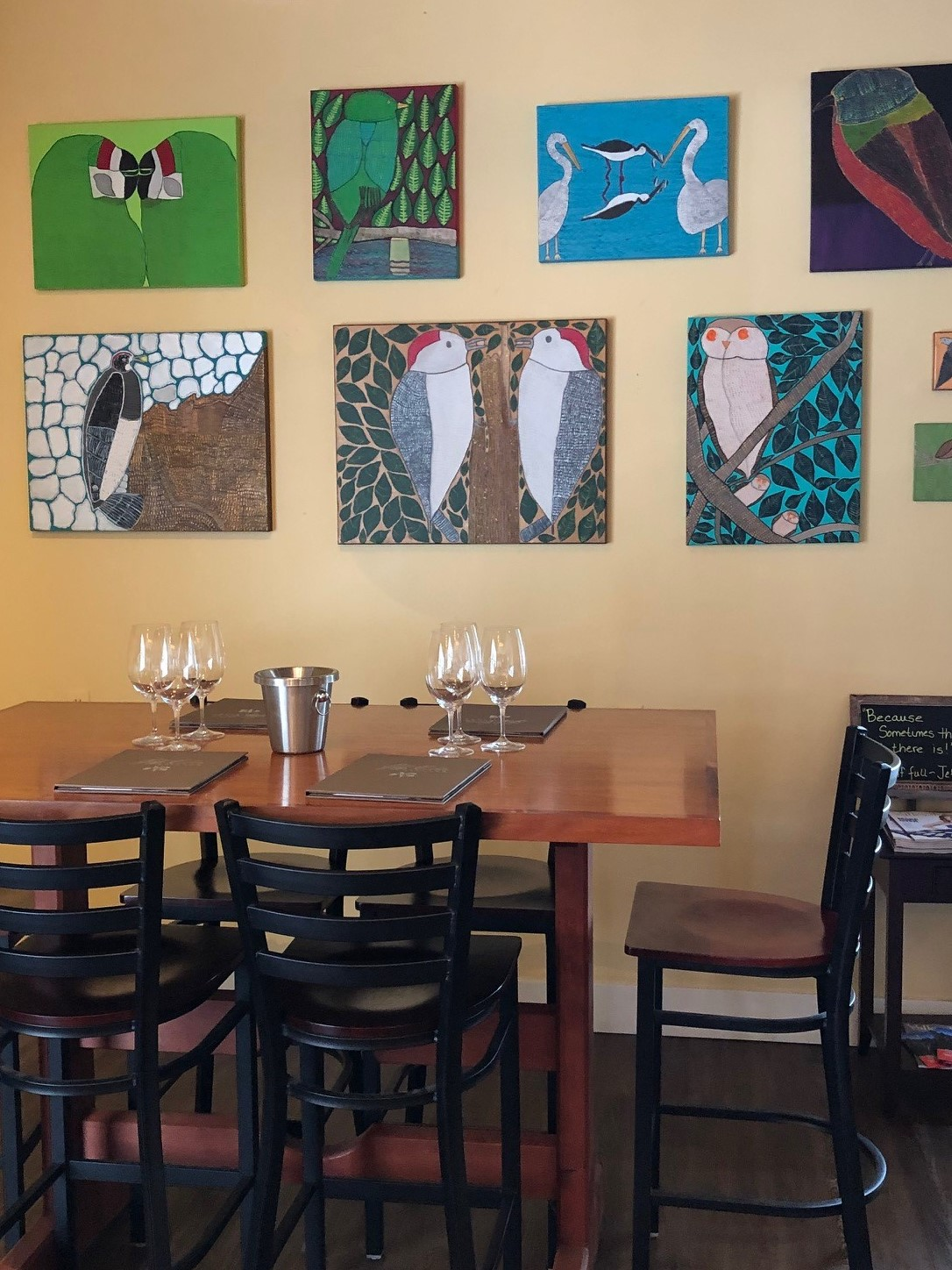 Wall of paintings at the Jeff Cohn tasting room May 2019.jpg