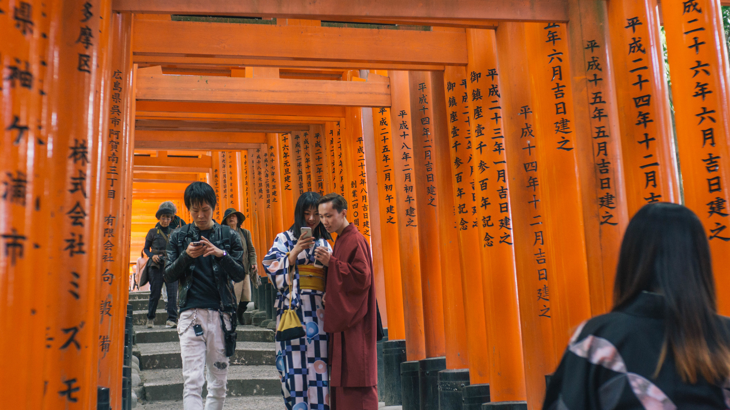 The torii path leading to another shrine. It's always funny to see the cross between old traditions and new technology, especially in the young folks in Japan.