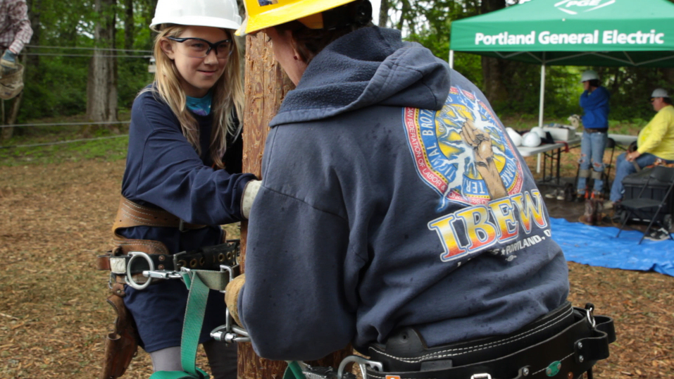 Future linewoman climbs her first pole at the Women in Trades Career Fair hosted by Oregon Tradeswomen, Inc. in Portland, OR.