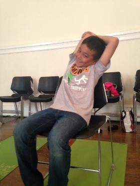 Cómo:  Mientras está sentado en su asiento, descruzar las rodillas y los tobillos y sentarse de altura. Traiga su brazo derecho hacia arriba al lado de su cabeza y doblar el codo para que su mano derecha está llegando por el centro de la espalda. Use su mano izquierda para sostener suavemente el codo derecho. Inhale, sentarse de altura. Exhale, y estirar hacia la izquierda, alargando su cuerpo de lado derecho y estirar su tríceps (bajo la parte del brazo superior). Mantenga y respira por 3-5 respiraciones. Repita 2-4 veces en ambos lados. Los niños pueden hacer sonidos de Sssshhhhhhh al estirar su cuerpo lateral o respiración del caballo (relajar los labios y soplar aliento creando una vibración a través de los labios, y un sonido relincho de caballo).   Beneficios:  alarga la columna y da espacio a sus pulmones y otros órganos.
