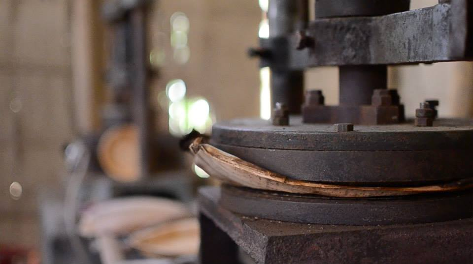 An arecanut leaf is transformed into a biodegradable and disposable dinner plate by one of three leaf plate making machines at the Das family production unit.