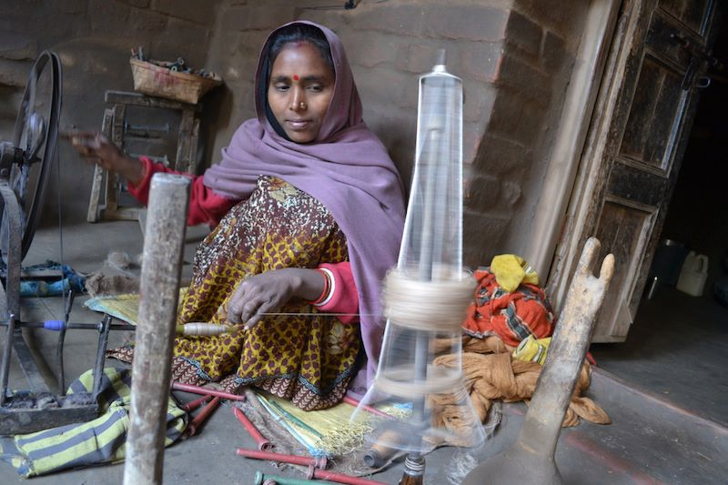 Eco Kargha weaver Poonam Devi prepares bobbins of silk thread. January 2013.