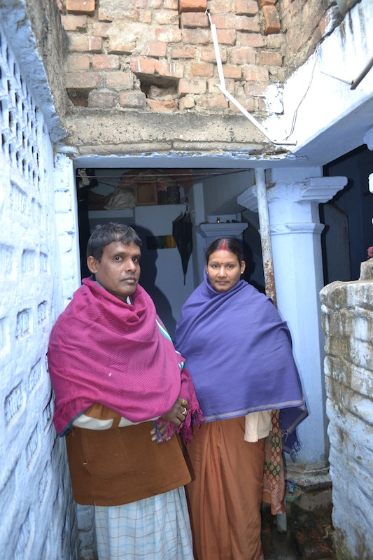 Sanjeev and his wife Rekha (right) stand in front of their home in the Champanagar slum. January 2013.