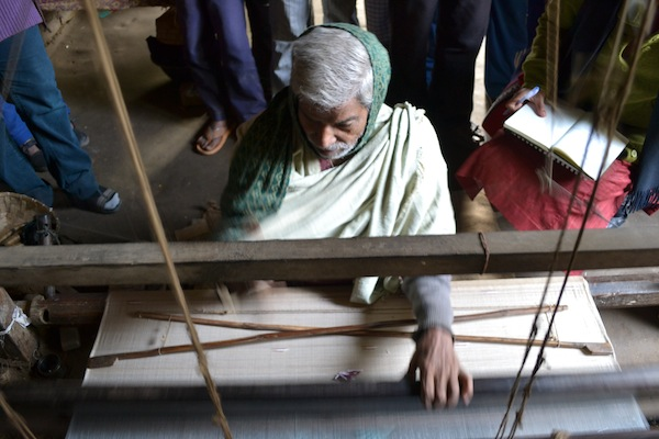 Bindu works on the loom to produce a silk scarf as members of the Upaya team look on. January 2013.