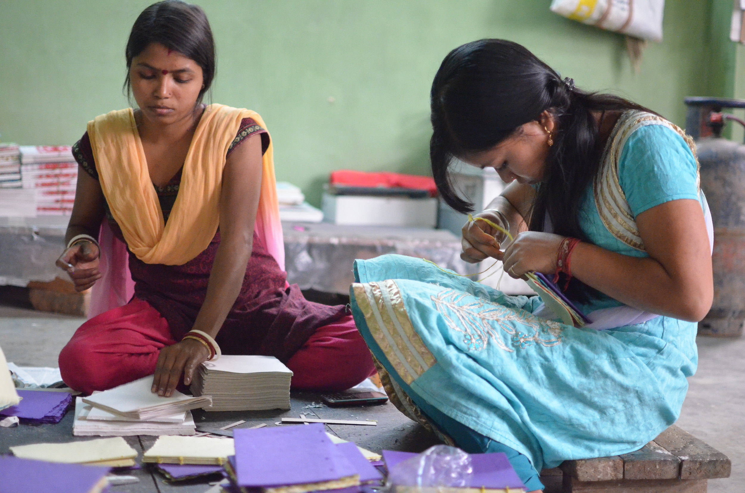 Rekha (left) and her colleague Minakshi (right) produce handcrafted notebooks in the Elrhino factory's design space