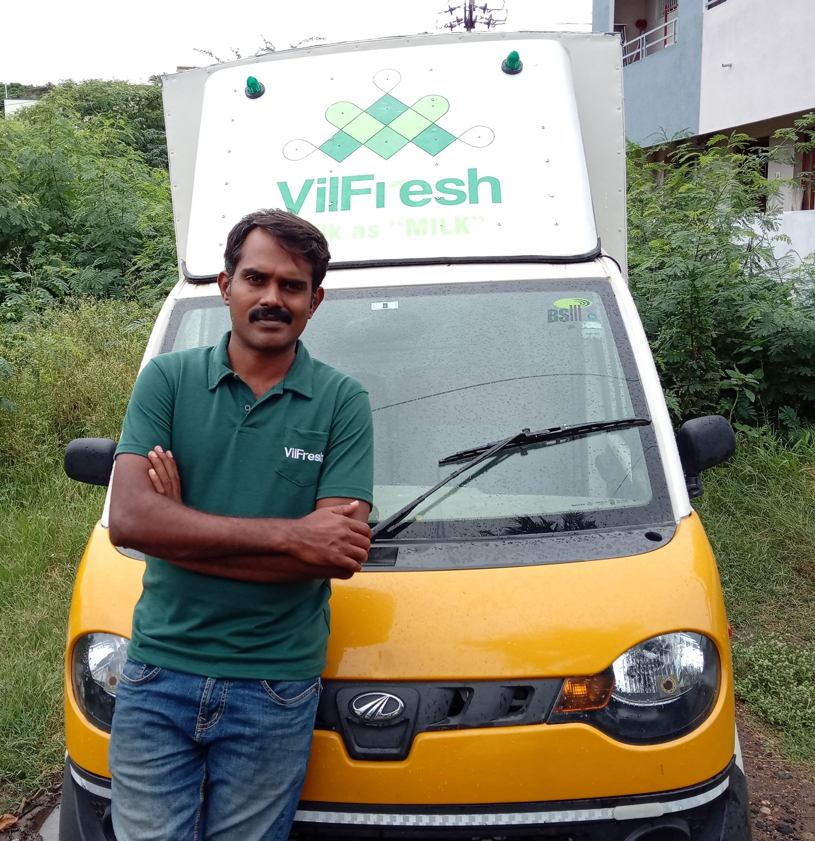 Selvakumar Varadharajan of Laymen Agro poses with a truck used to distribute fresh milk and produce from Indian villages directly to urban cities.