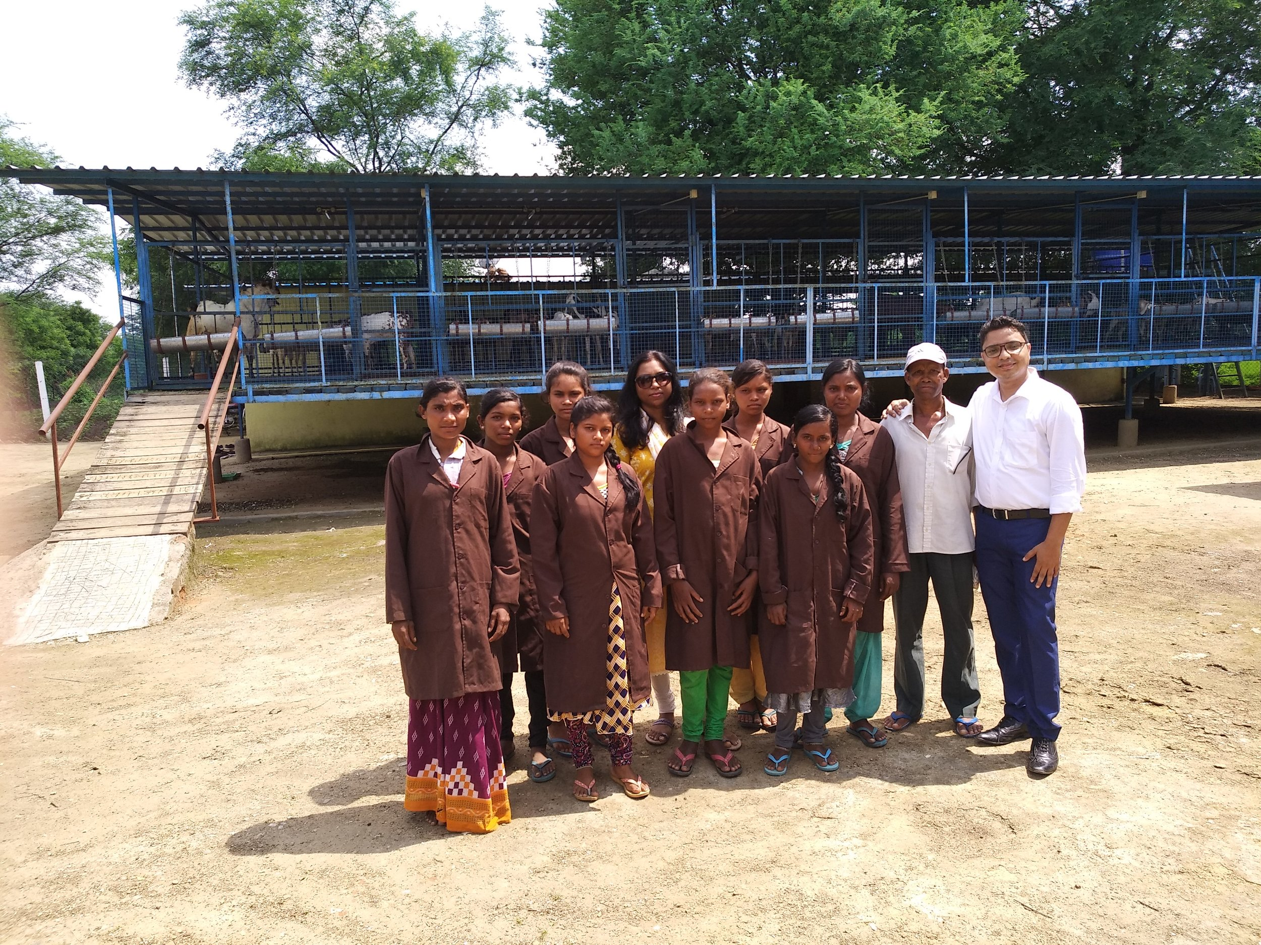 Jayanti (back, center) with a group of Manikstu Agro jobholders in front of the company's goat shelter.