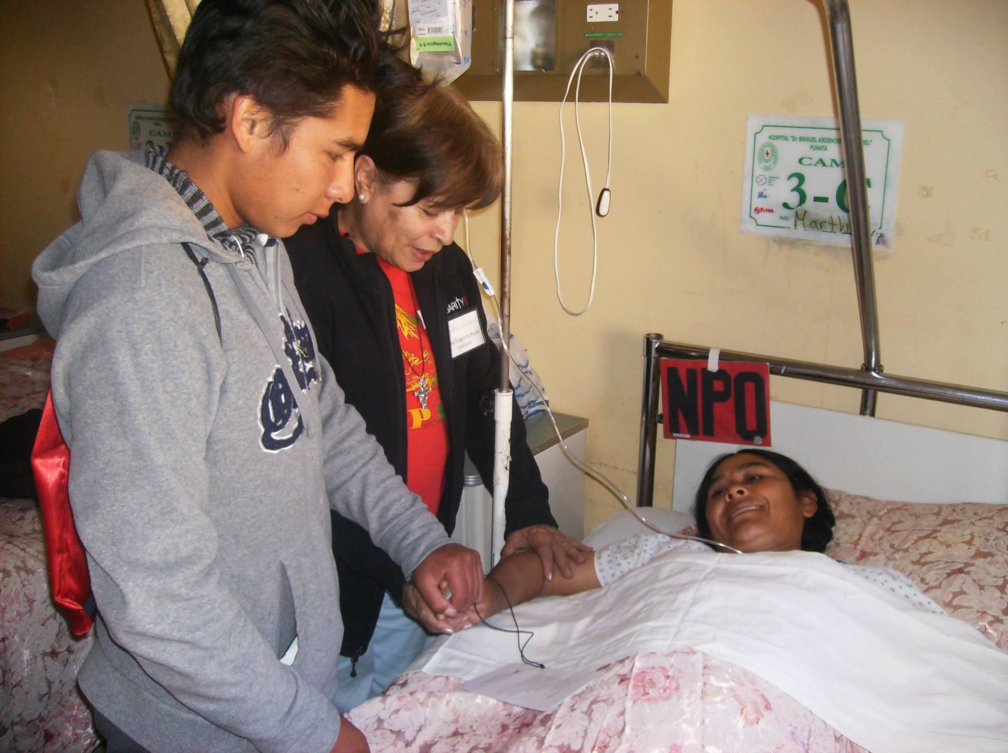 Puente de Solidaridad Board Member and Chaplain, María Eugenia Rojas, prays with a patient and her son.