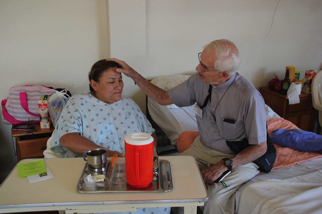 Fr. Bob visiting with a patient from the 2015 Multi-Specialty Mission Trip