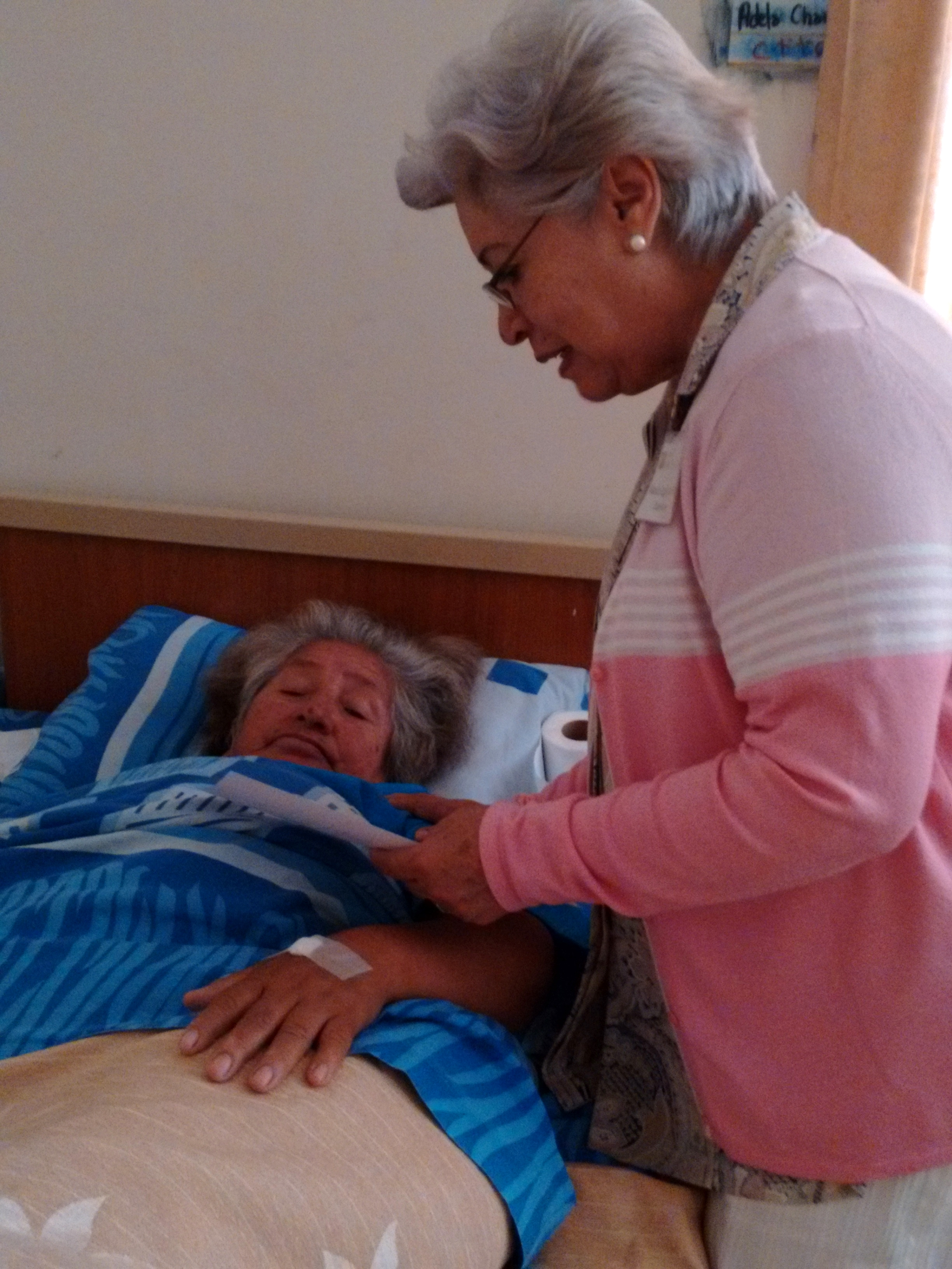 Alma and Maria Eugenia Rojas (trip chaplain) prays together after her successful surgery.