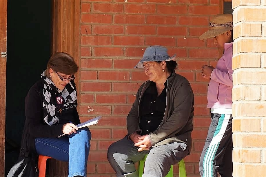 Maria Ines Uriona, coordinator of medical programs and lead social worker from Puente de Solidaridad (left), meets with a patient before her surgery in Mizque.