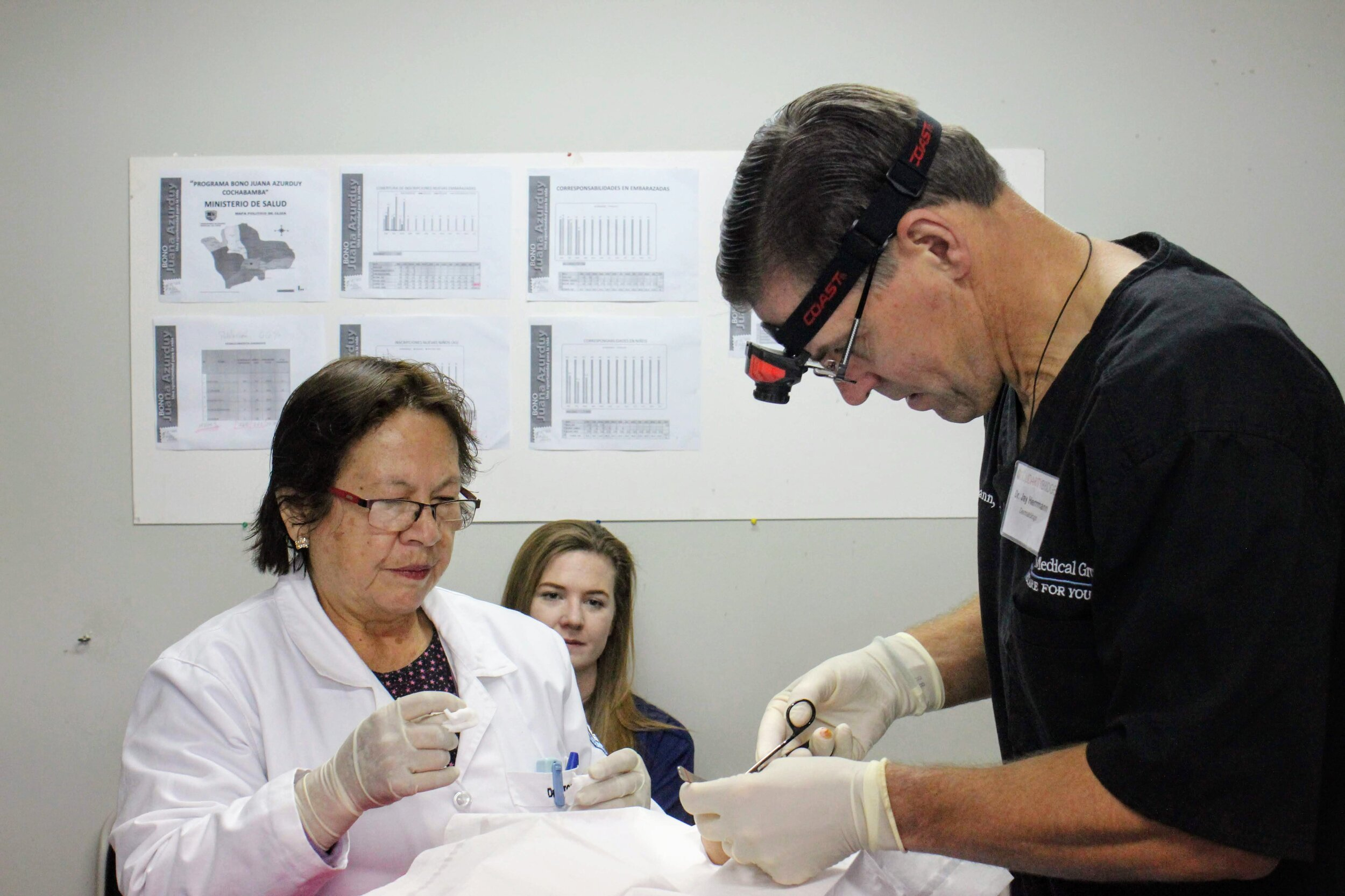 Dr. Torrico assists during a dermotology procedure