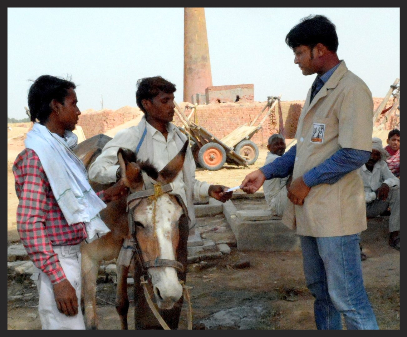 This Brooke veterinarian in India is treating a donkey and discussing her care with her owners.