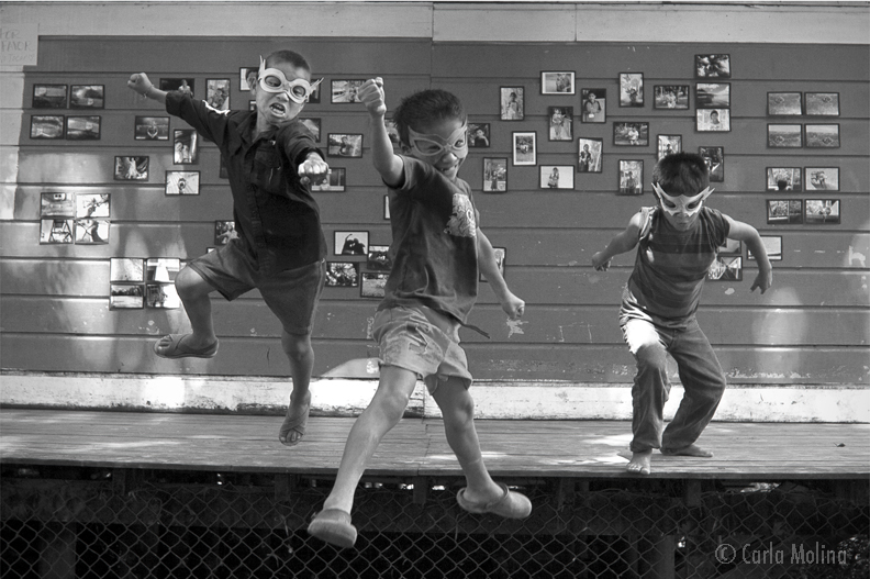 MIGHTY boys in flight  (rio Dulce, Guatemala)  11 X 17 PRINT $55  20 X 30 PRINT $105  CHILDHOOD.  THREE YOUNG BOYS LET THEIR INNER SUPERHERO OUT AS THEY JUMP FROM THE DECK IN FRONT OF THE MIGHTY ME KIDS PHOTOGRAPHY EXHIBITION AT CASA GUATEMALA. © CARLA Molina