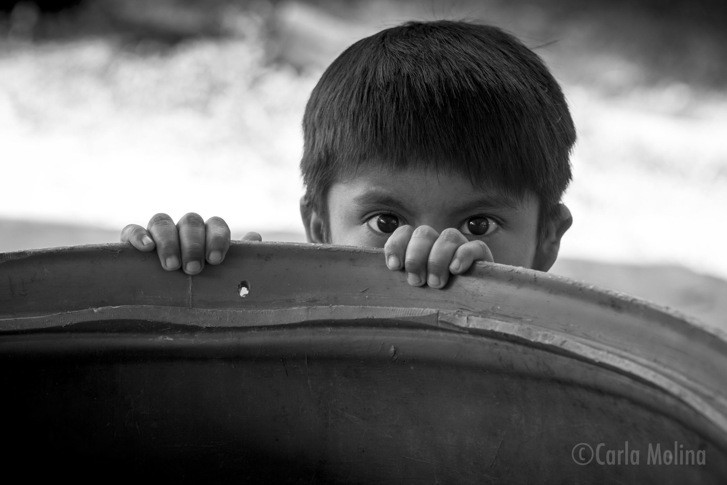 Boy Peeking  (rio Dulce, Guatemala)  11 X 17 PRINT $55  20 X 30 PRINT $105  Big eyes filled with curious mischief peek out from behind a barrel. © Carla Molina