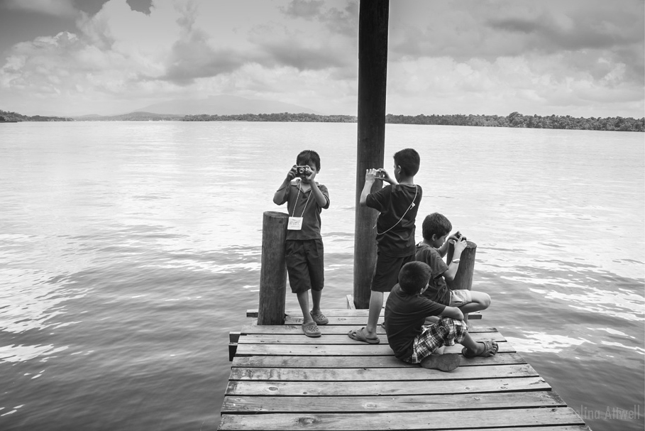 Mighty Me Photographers - Boys on the water   (Rio Dulce, Guatemala)  These four boys rushed to the end of the dock when they got their cameras.  THey spent an hour photographing canoes and boats as they paddled and motored by. The river leads to the sea an hour down stream.  © Angelina Attwell