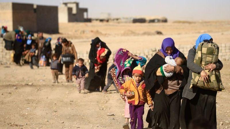 Displaced people fleeing from Islamic State militants in Tahrir neighborhood walk in Mosul, Iraq. (Thaier Al-Sudani / Reuters)