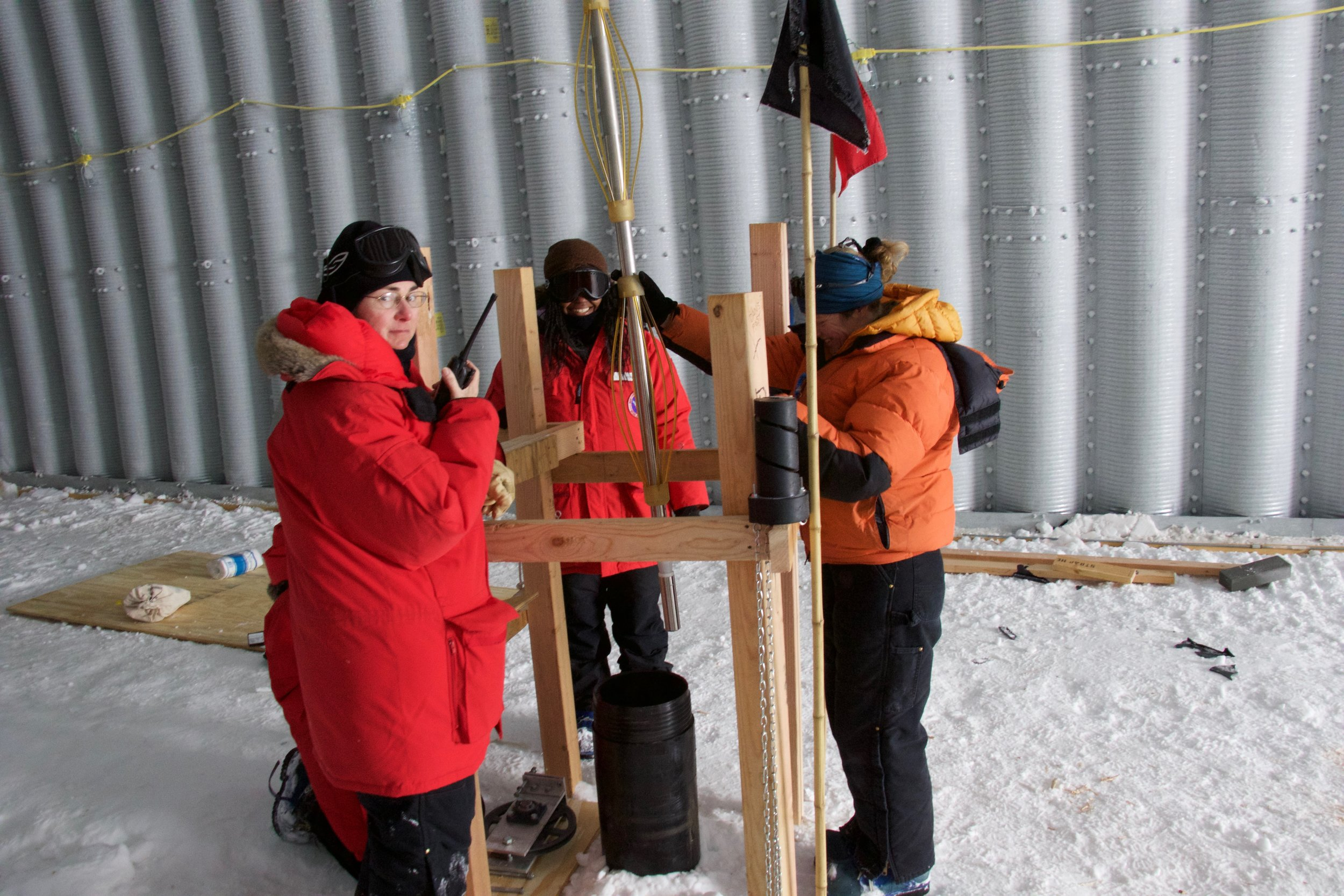 Inside the arch, Rachel, Anny, and Erin lower the Acoustic Televiewer (AKA Batwoman) into the borehole.