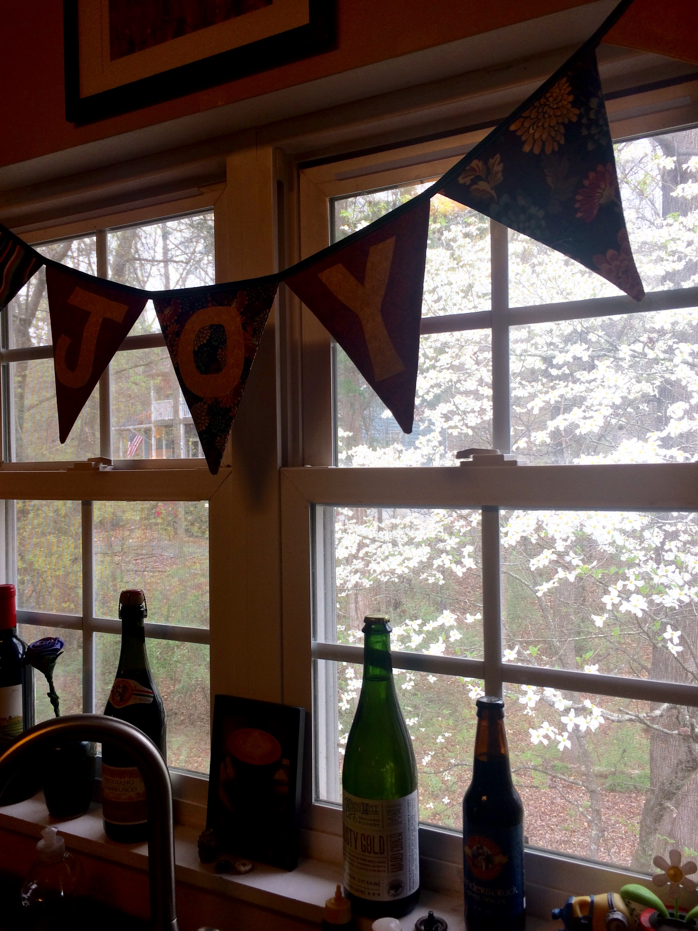 "The view from my kitchen sink, with our lovely dogwood tree out back and my banner that says ""Joy."""