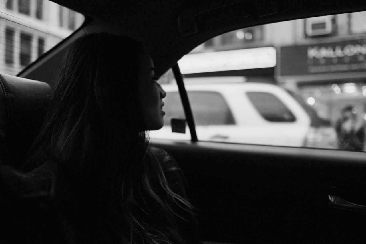 Black and white image of girl in the back of a car