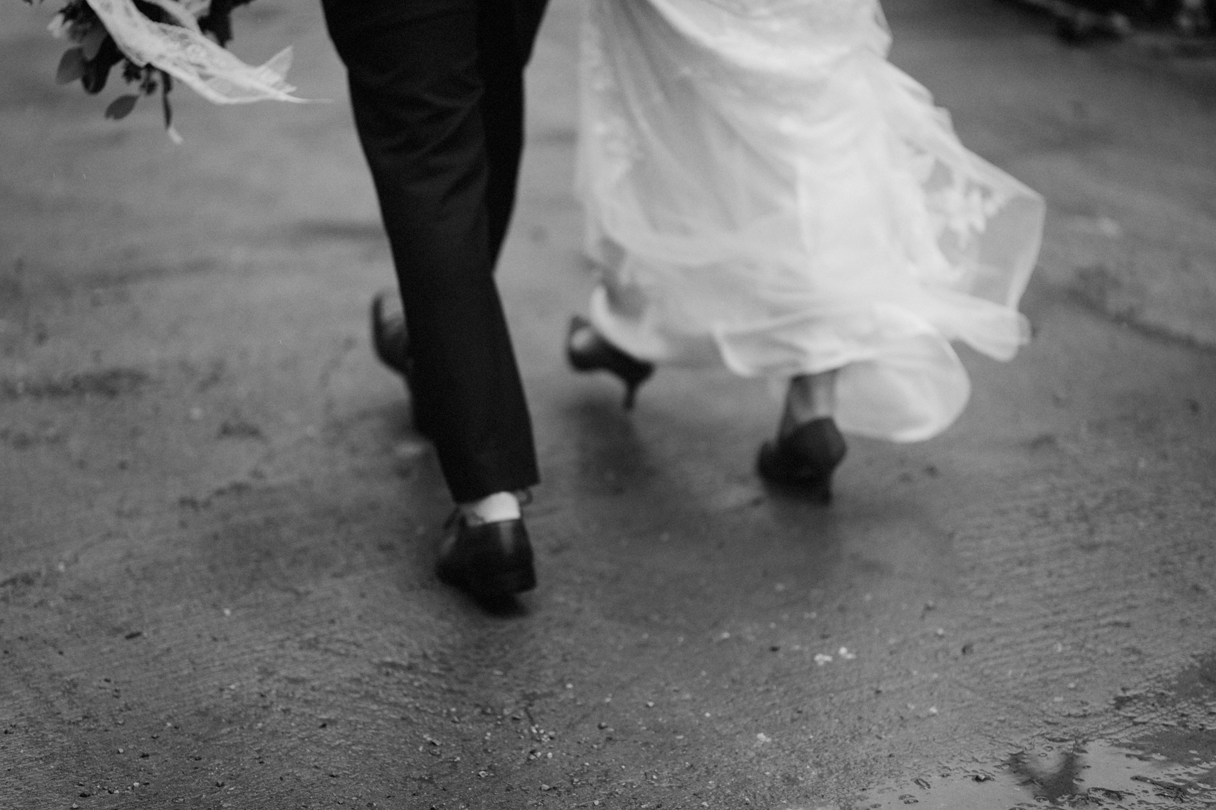 Wedding couple walking in the rain