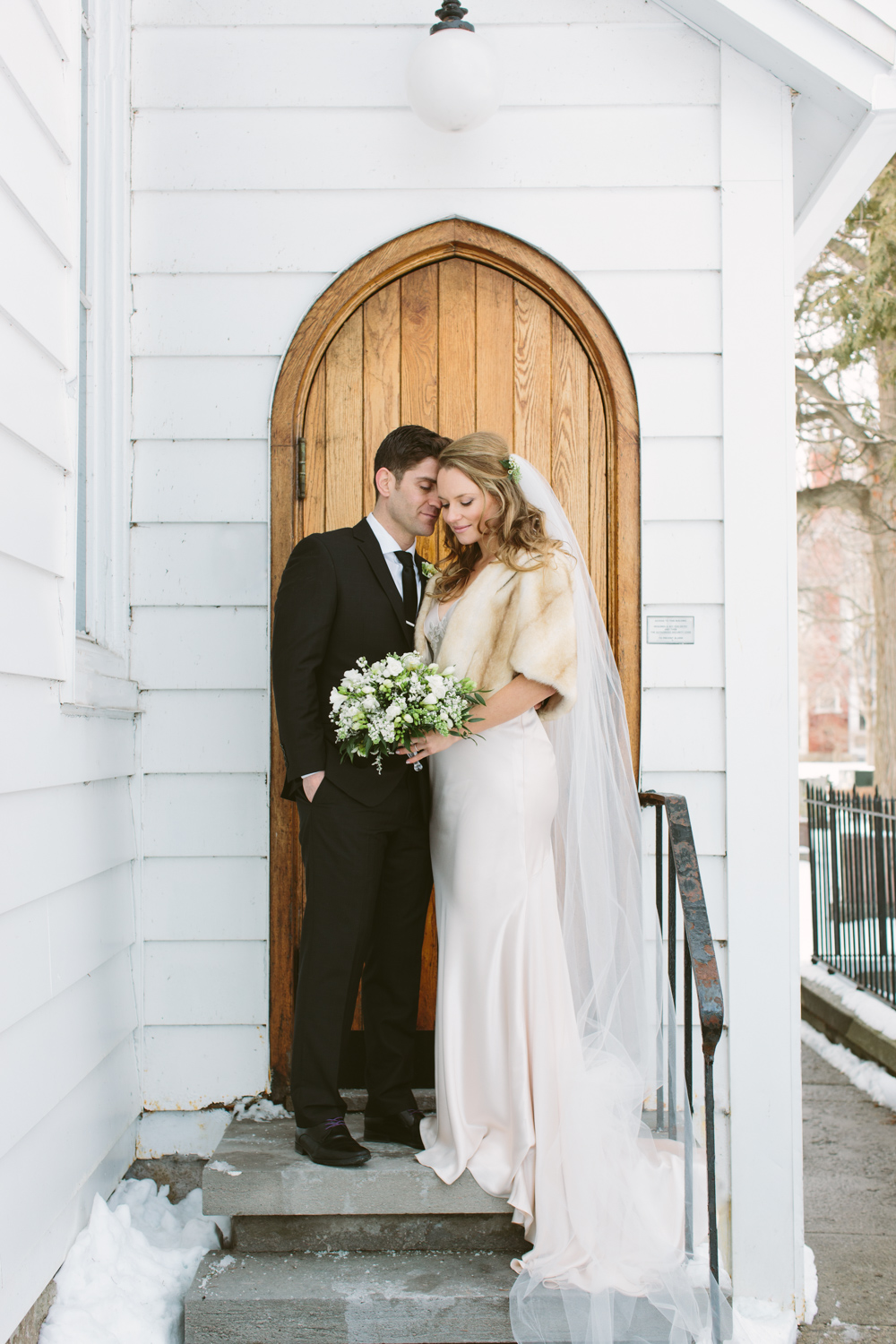 Couple standing  in the doorway of a small white church