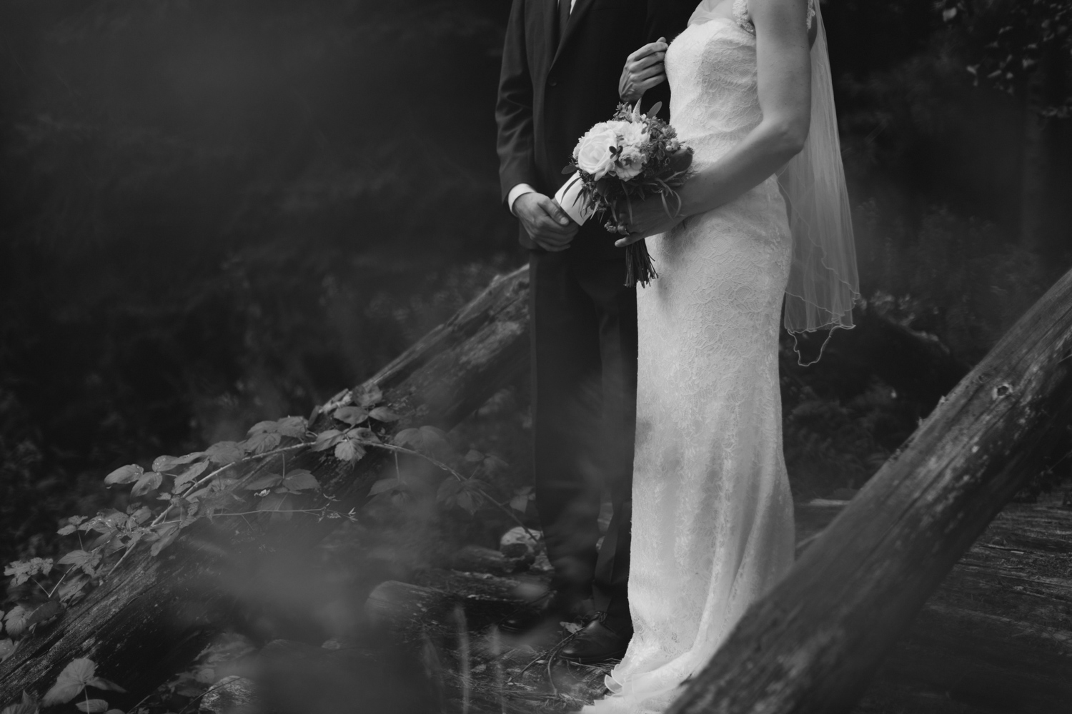 Black and white image of couple standing on a bridge
