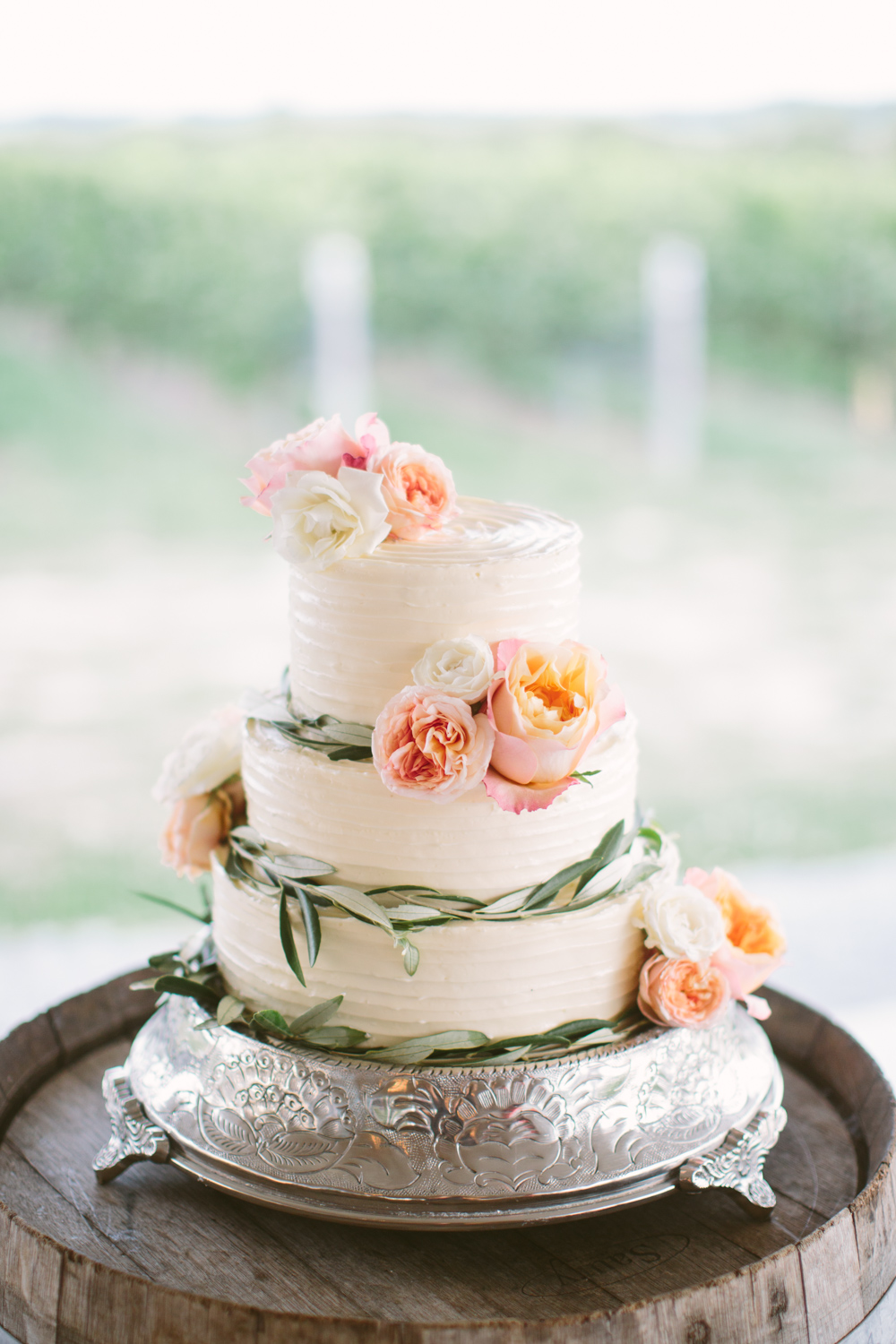 Simple white cake with olive leaves and flowers on an oak wine barrel