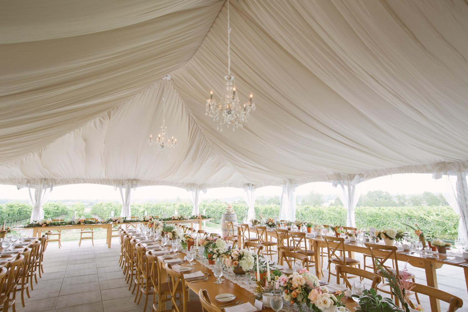 Draped tent harvest tables wedding reception