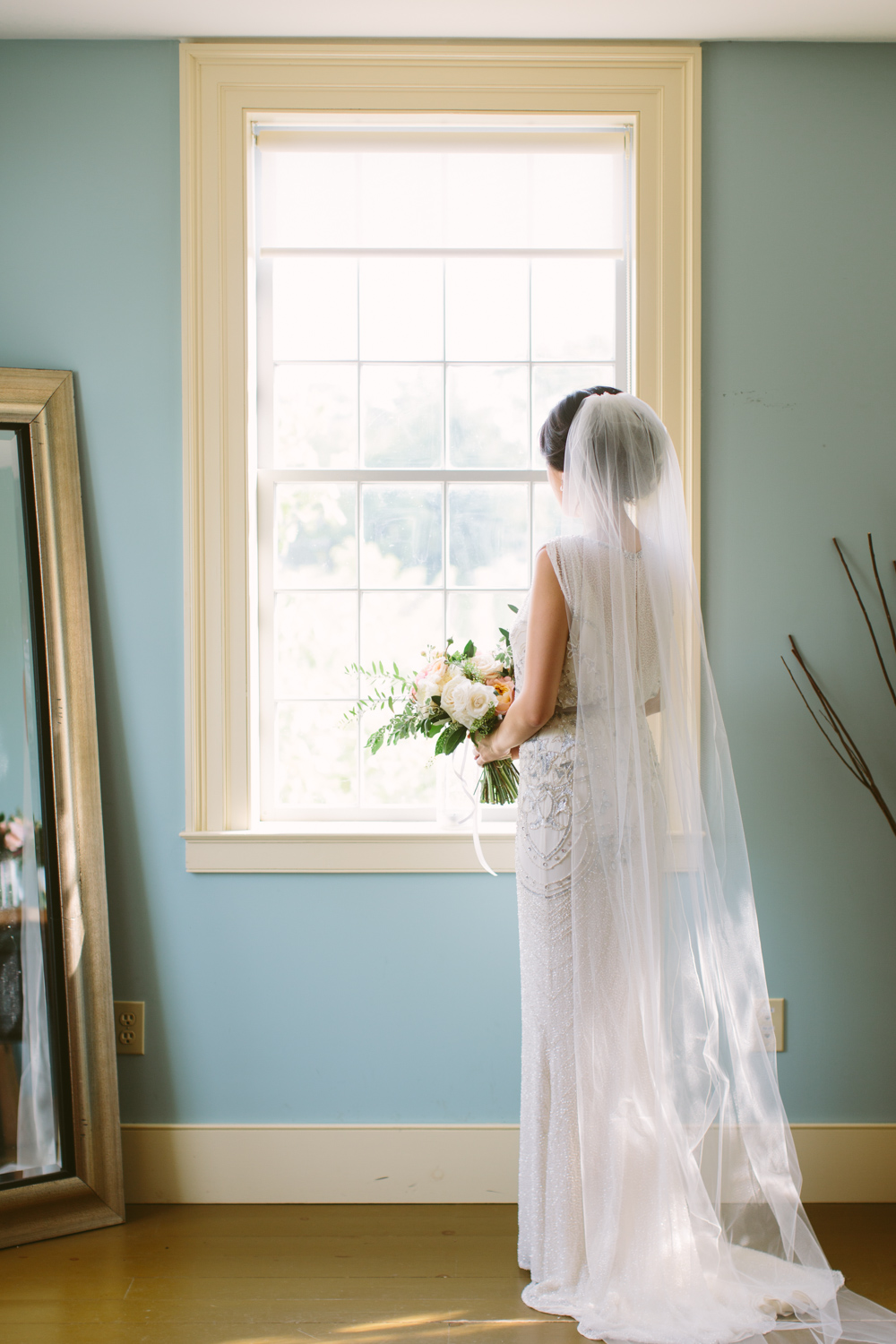 Bride wearing a Jenny Packham dress and long veil looking out a window