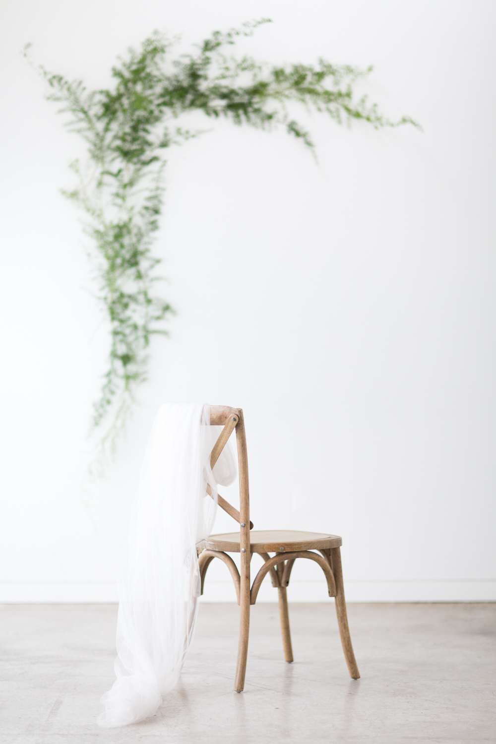 A long simple veil draped over a cross-backed wooden chair