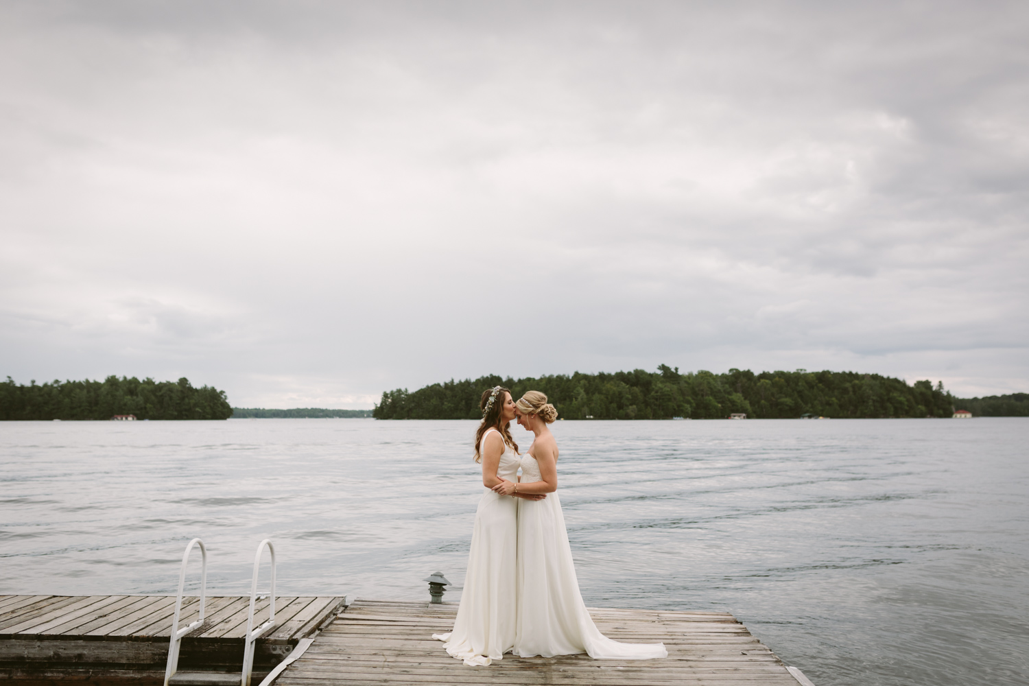 Brides embracing on a dock in Muskoka