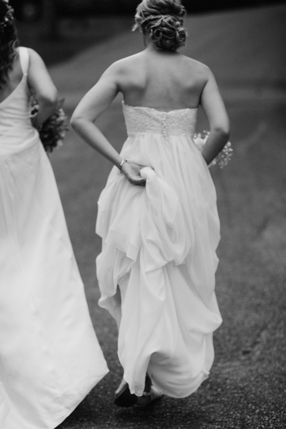 Bride holding her dress and walking uphill