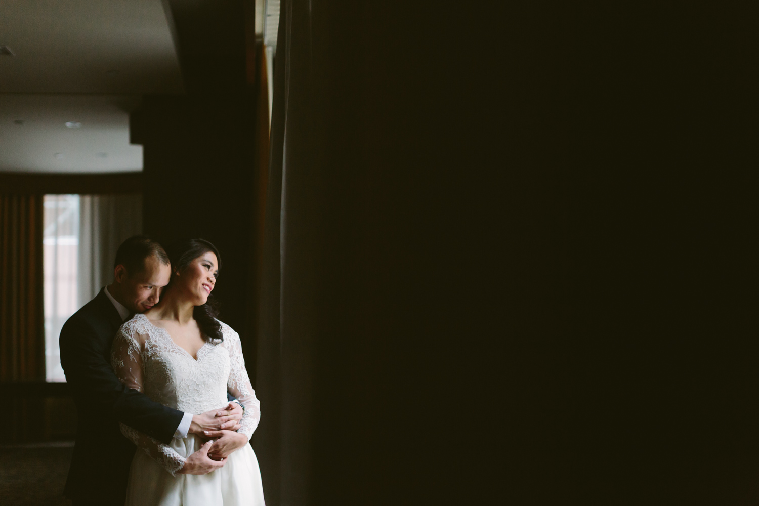Groom holding bride in front of a window