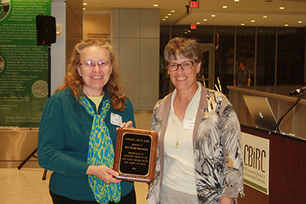 Gale Vermeulen (L) is presented an Outstanding Service Award by Kelen Panec.