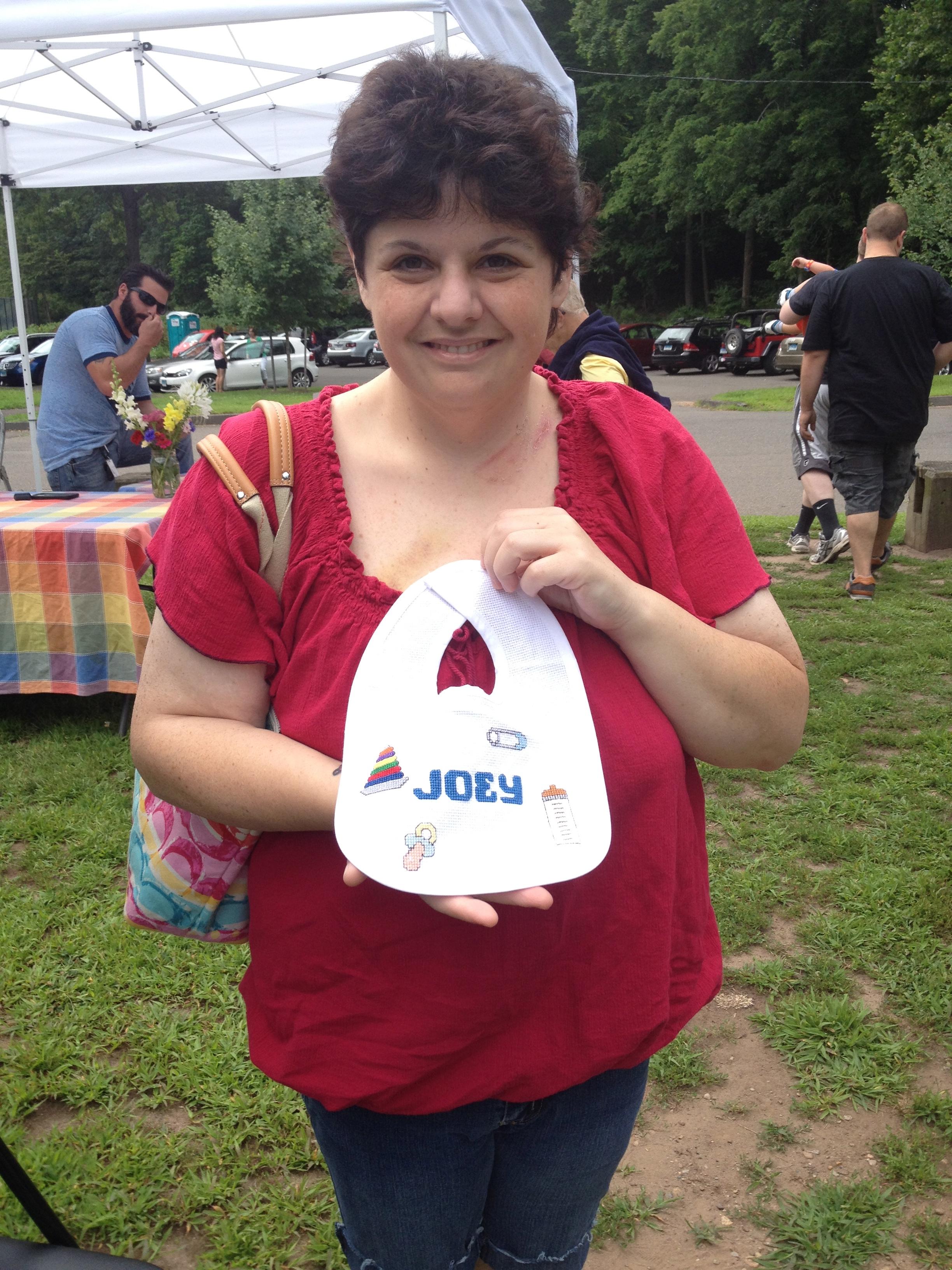 Anastacia D'Aiuto donates a cross-stitched bib to MMoAA at the Edgewood Park Farmer's Market
