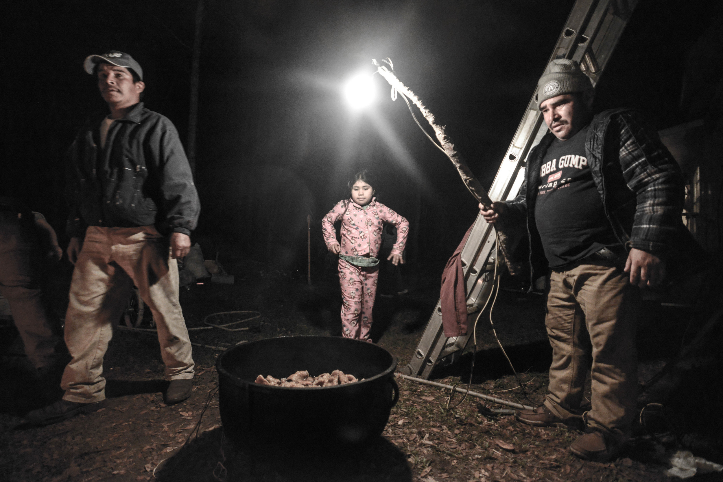 Suleyma looks onto a pot of boiling pig skin as they get ready for a birthday celebration in honor of Maria, her grandmother. Workers from neighboring homes and their church were invited to eat, drink and celebrate on a Friday night at their home.