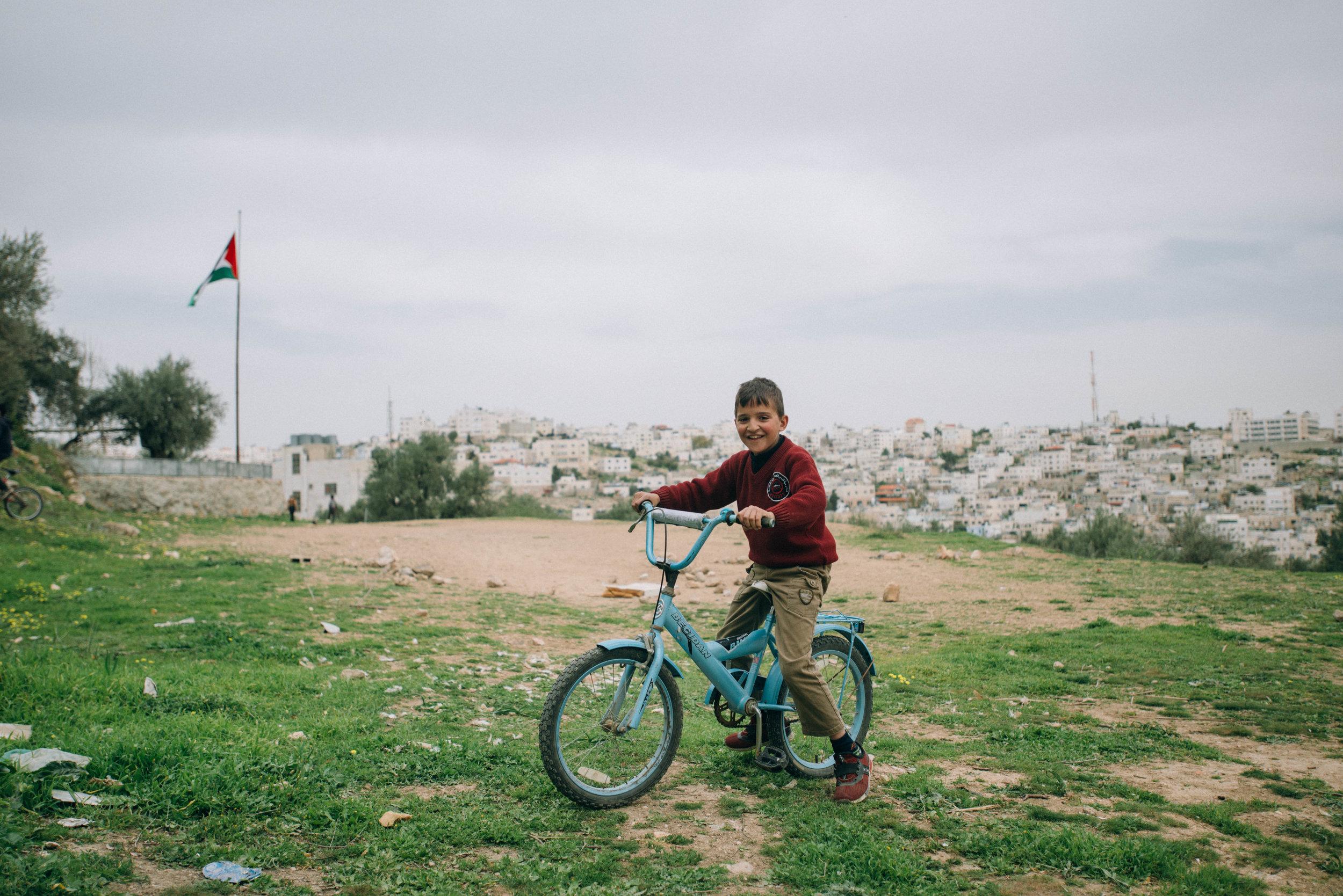 A boy rides his bike in Hebron, Palestine.