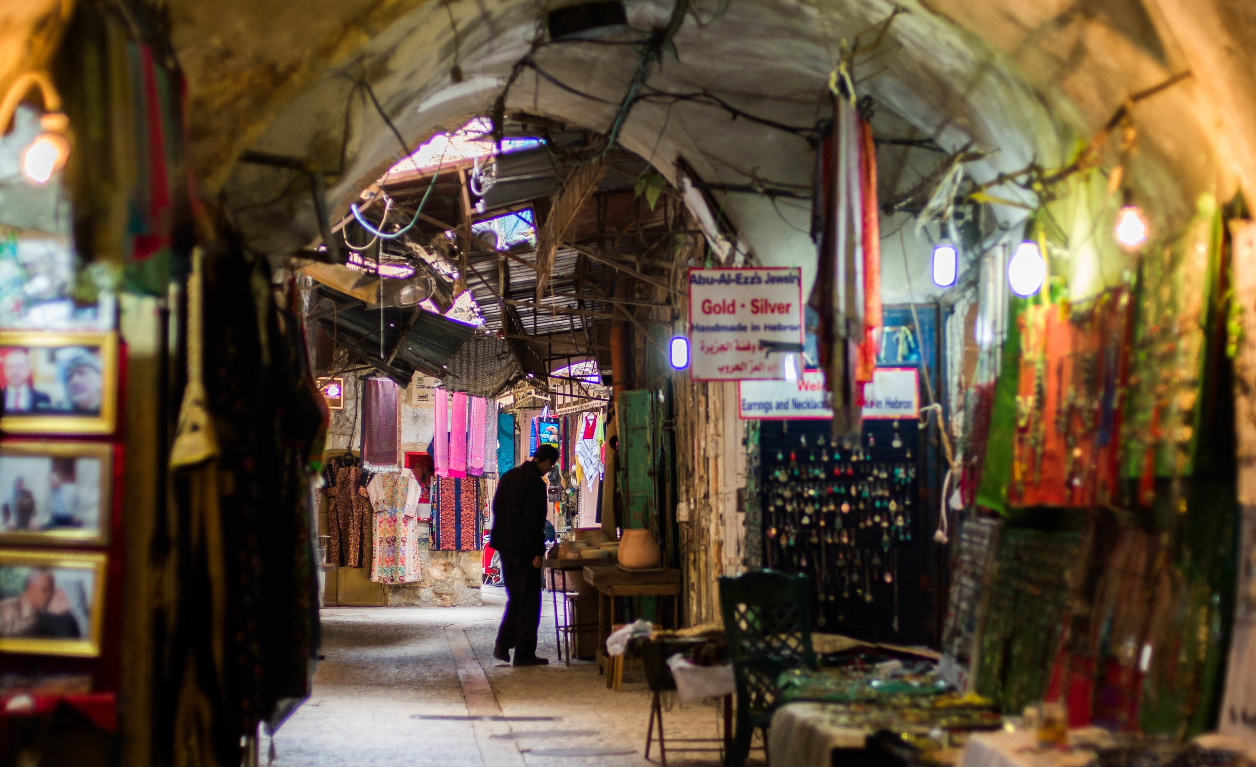 A Palestinian man peruses through his items in his shop a little down aways from the Women in Hebron cooperative table in the Old City of Hebron market.