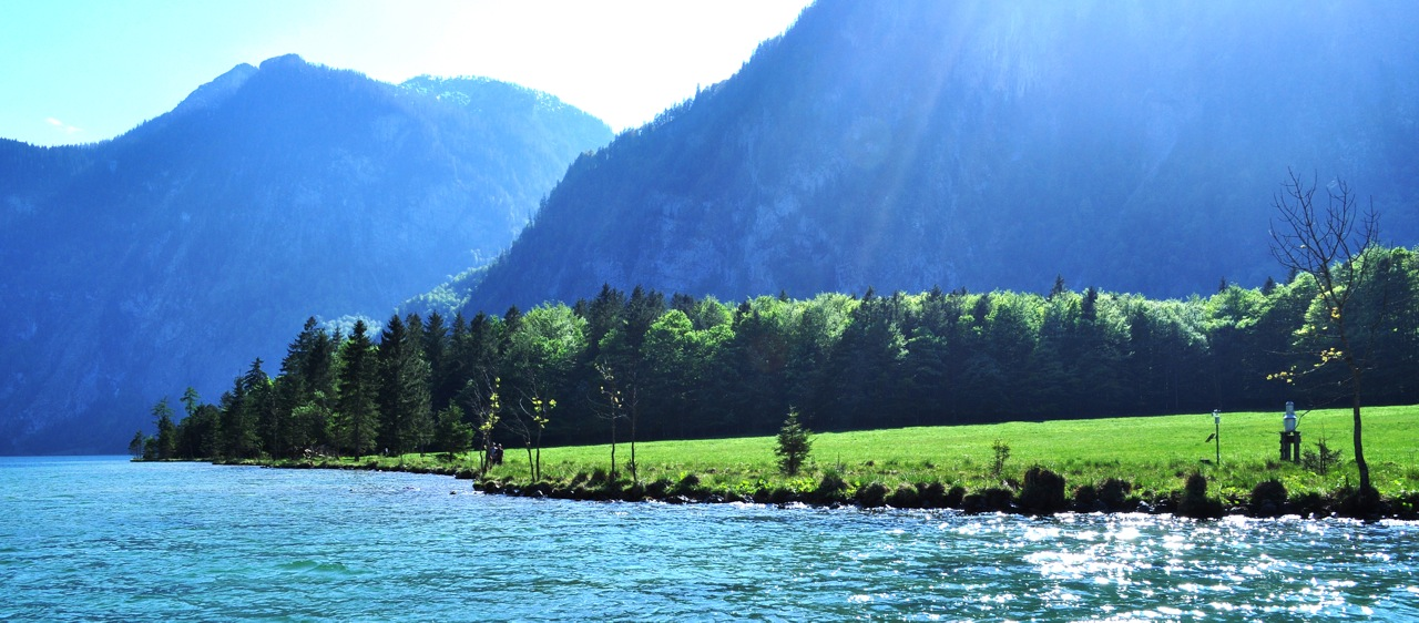 Sun rays streaming through. Koenigssee. Germany.